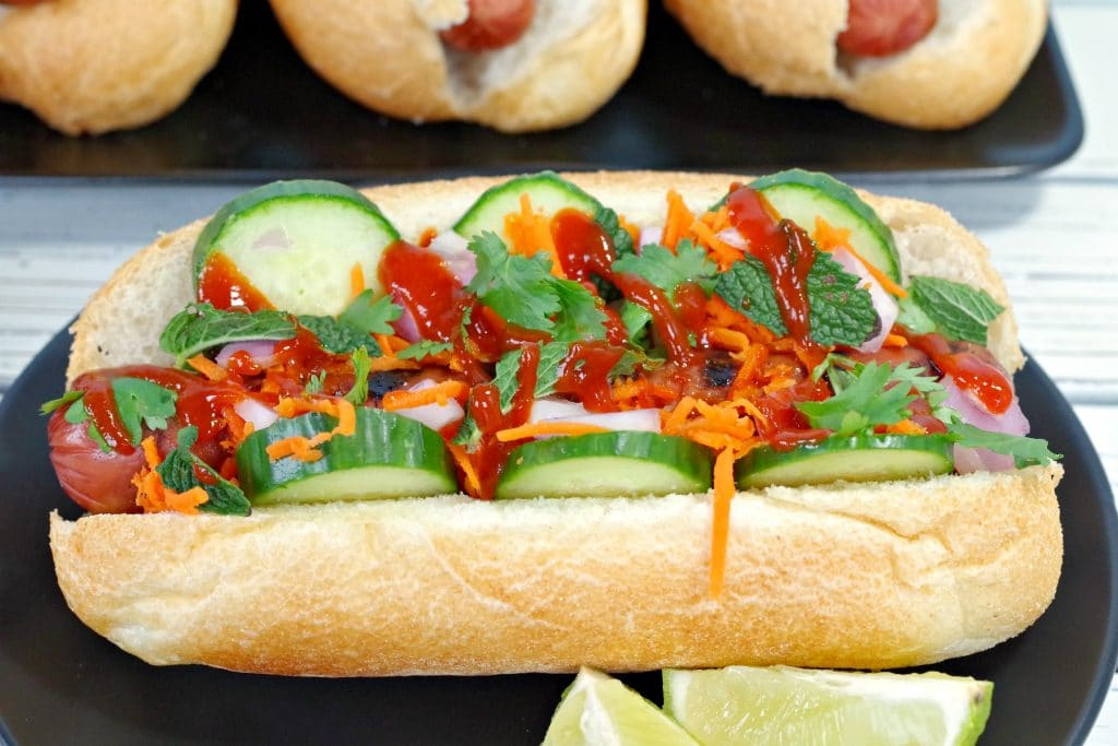 Side view of Banh Mi Turkey Hot dog on black plate with lime wedges