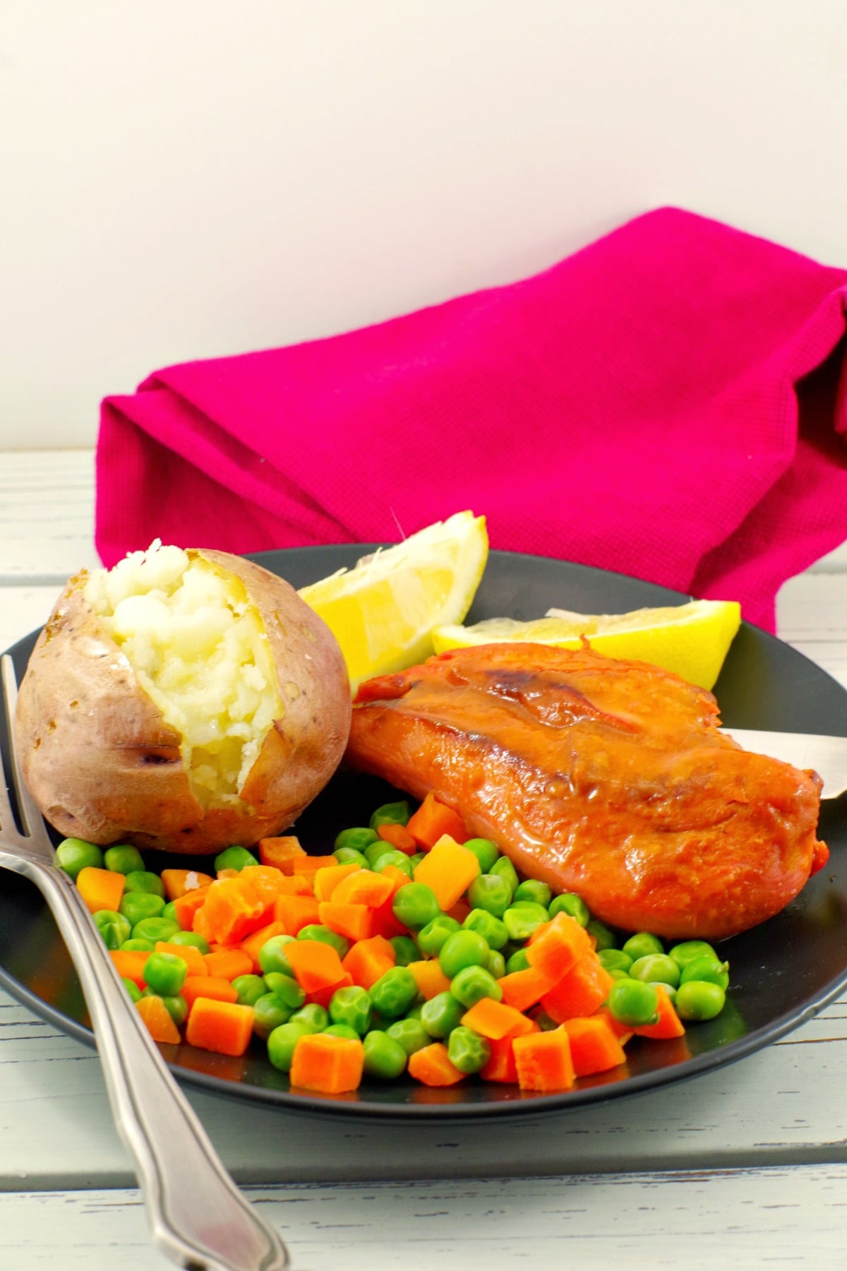 Monterey chicken on plate with baked potato and mixed vegetables