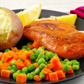 Monterey chicken on plate with baked potato and mixed vegetable