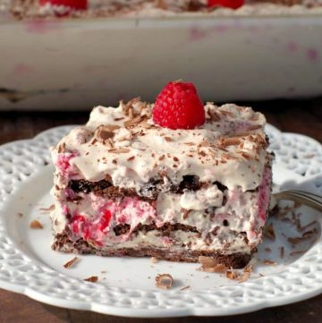 A piece of raspberry dulce de leche icebox cake on an elegant white plate with cake in background