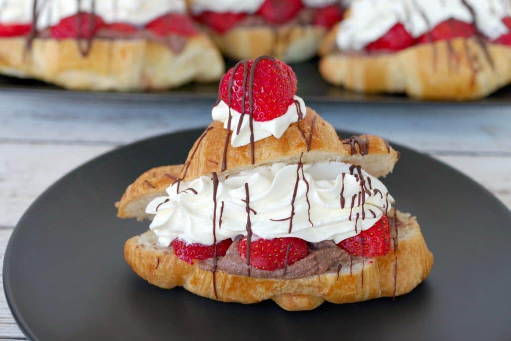 Strawberry Tiramisu eclair on black plate with eclairs in the background