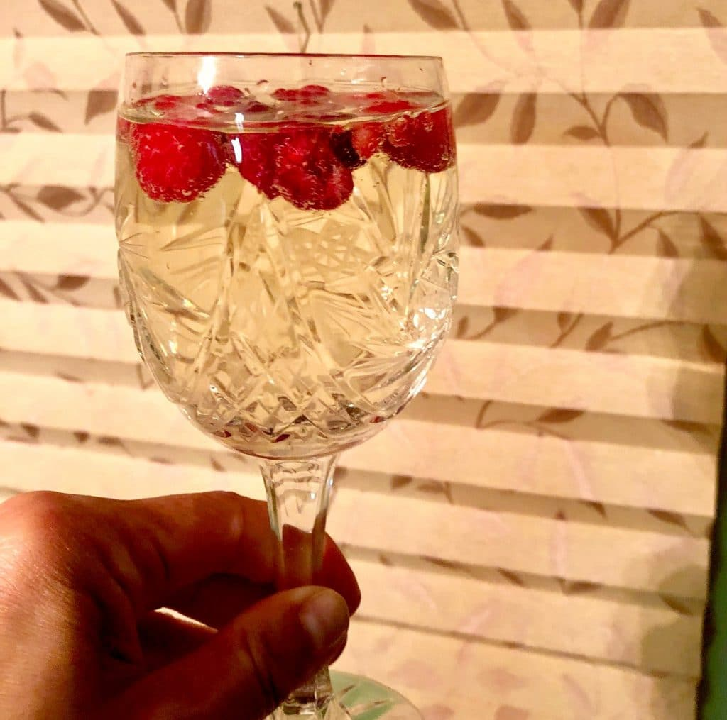 Glass of white wine with frozen raspberries as ice cubes