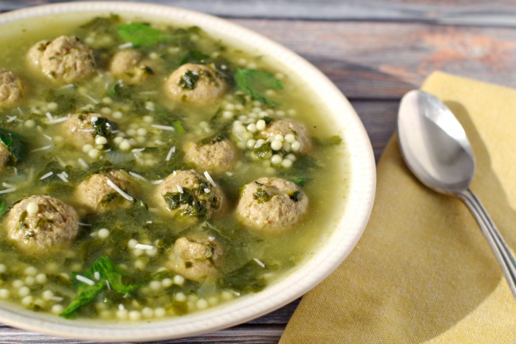 Easy Italian Wedding soup in beige bowl with yellow napkin
