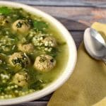 Easy Italian wedding soup with frozen meatballs on a bluish wooden background with a yellow napkin and spoon