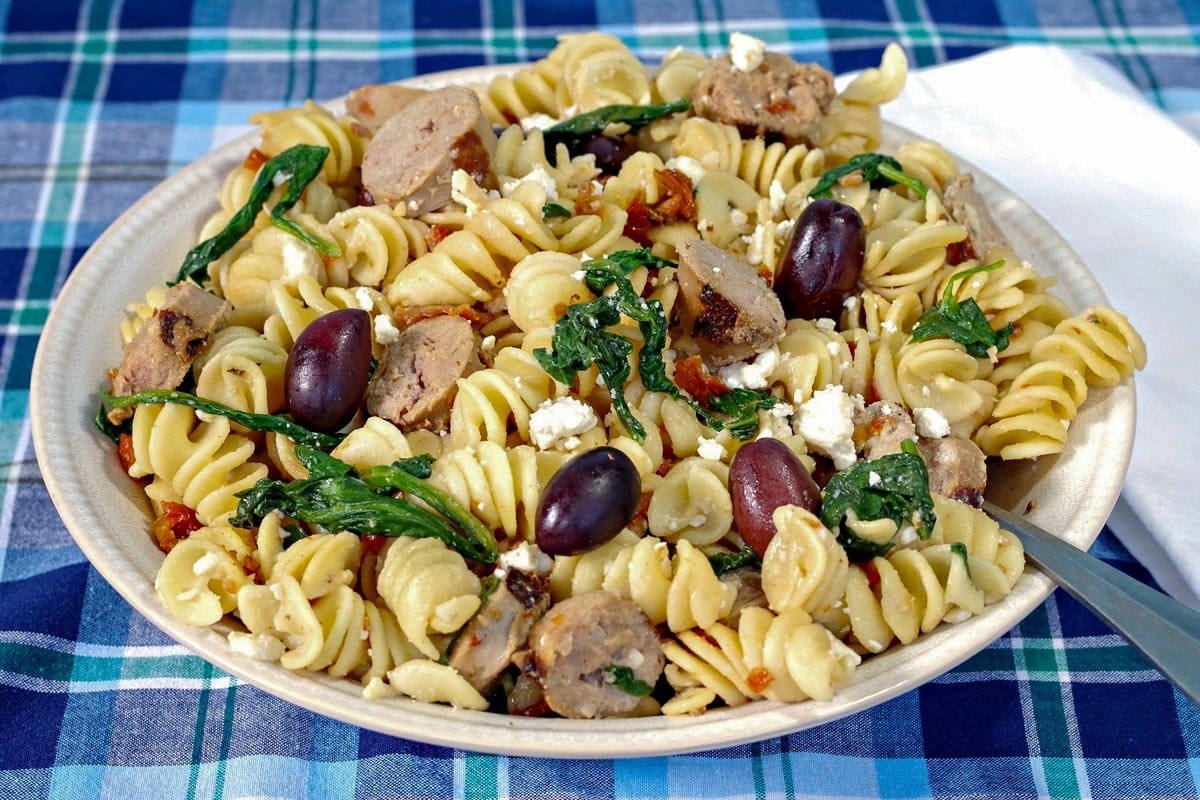 Greek pasta in a blue bowl with a brown wooden spoon