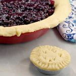 No Fail Pie Crust filled with Saskatoon berry pie filling and mini pie in front