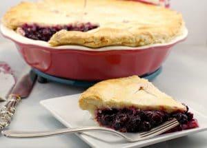 Saskatoon berry pie on plate with whole pie in background