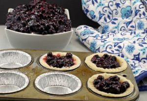 Saskatoon berry pie filling in tarts with bowl of pie filling in background