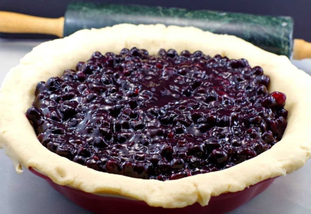 Saskatoon berry pie filling poured into unbaked pie shell