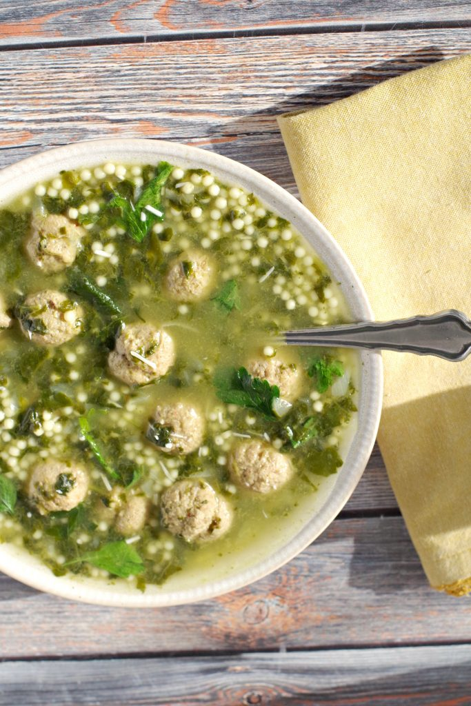 Bowl of Easy Italian Wedding soup with spoon and yellow napkin