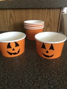 Drawing a jack o'lantern face on each orange cup