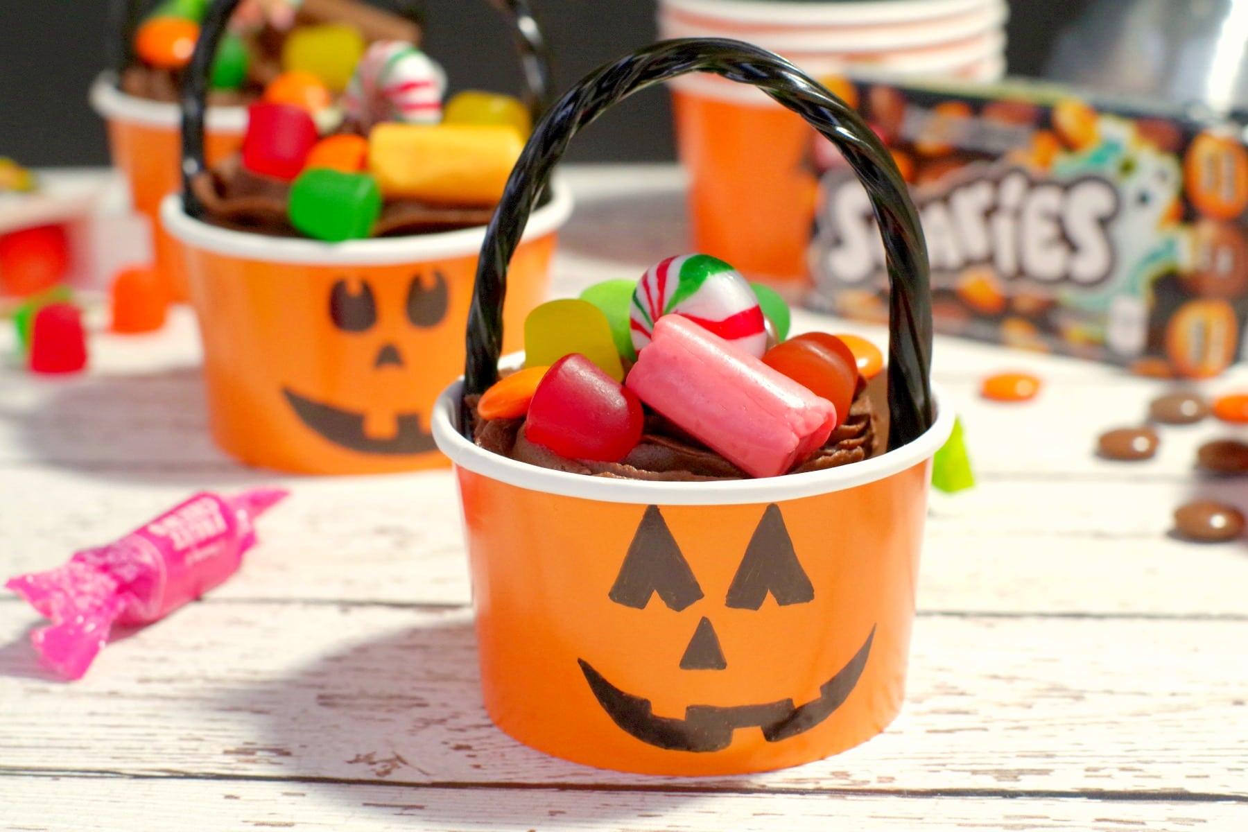 Halloween Jack o'latern bucket cupcake with candy strewn around