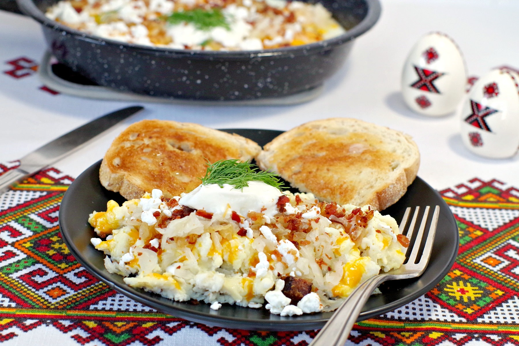 Scrambled Ukrainian style eggs on a black plate in foreground with pan of fried Ukrainian style eggs in background