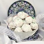 Almond Snowball cookies in a blue Christmas cookie tin, with ribbon around it