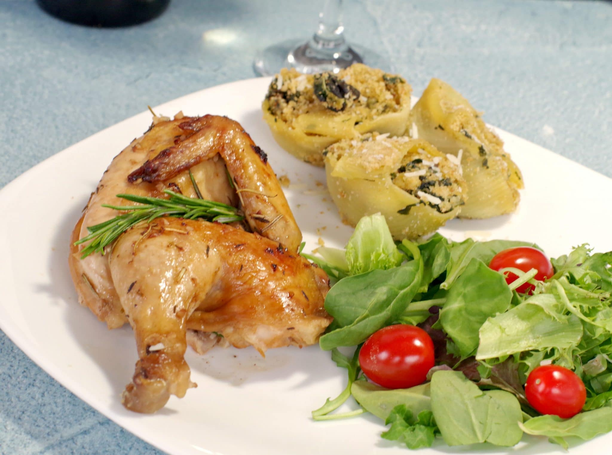 Cornish Hen on a plate with pasta and salad