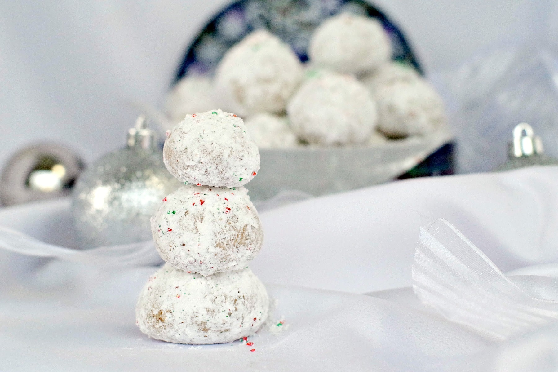 Gingerbread Snowball Cookies piled up to look like a snowman