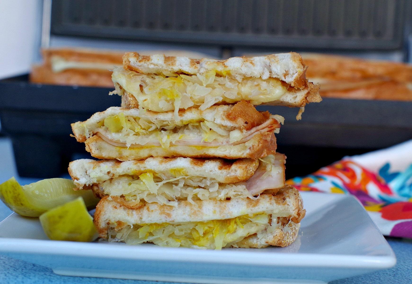 Turkey Reuben Panini on white plate in front of panini press