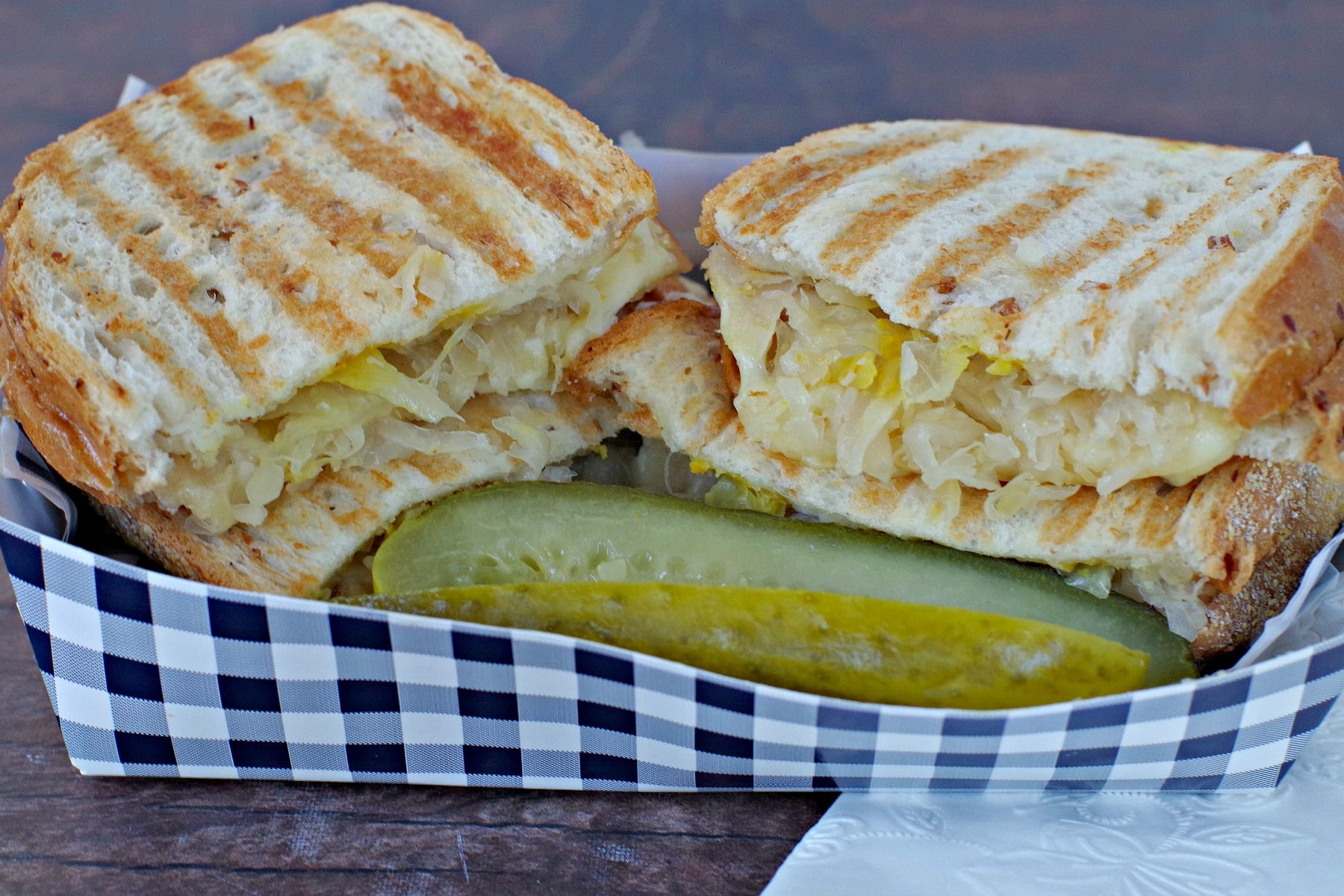 Turkey Reuben sliced in half in a paper blue checkered box with a pickle in front