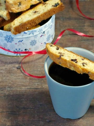 Black forest biscotti on a blue mug with Christmas tin of more biscotti in background