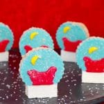 snow globe rice krispie treats on a black platter with red background
