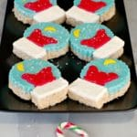 Rice Krispie Snow Globes on black tray with candy canes