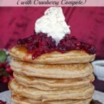 stack of gingerbread pancakes with cranberry compote and whipped cream on top
