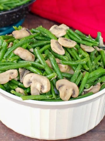 green beans and mushrooms in a white casserole dish on brown surface with red oven mitt in background