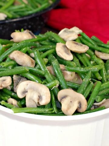green beans and mushrooms in a white round casserole dish