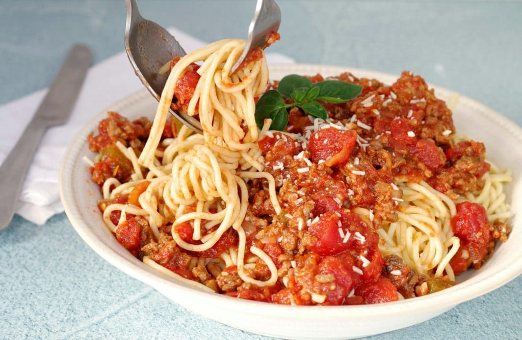 Spaghetti and meat sauce with spaghetti being twirled on fork with spoon