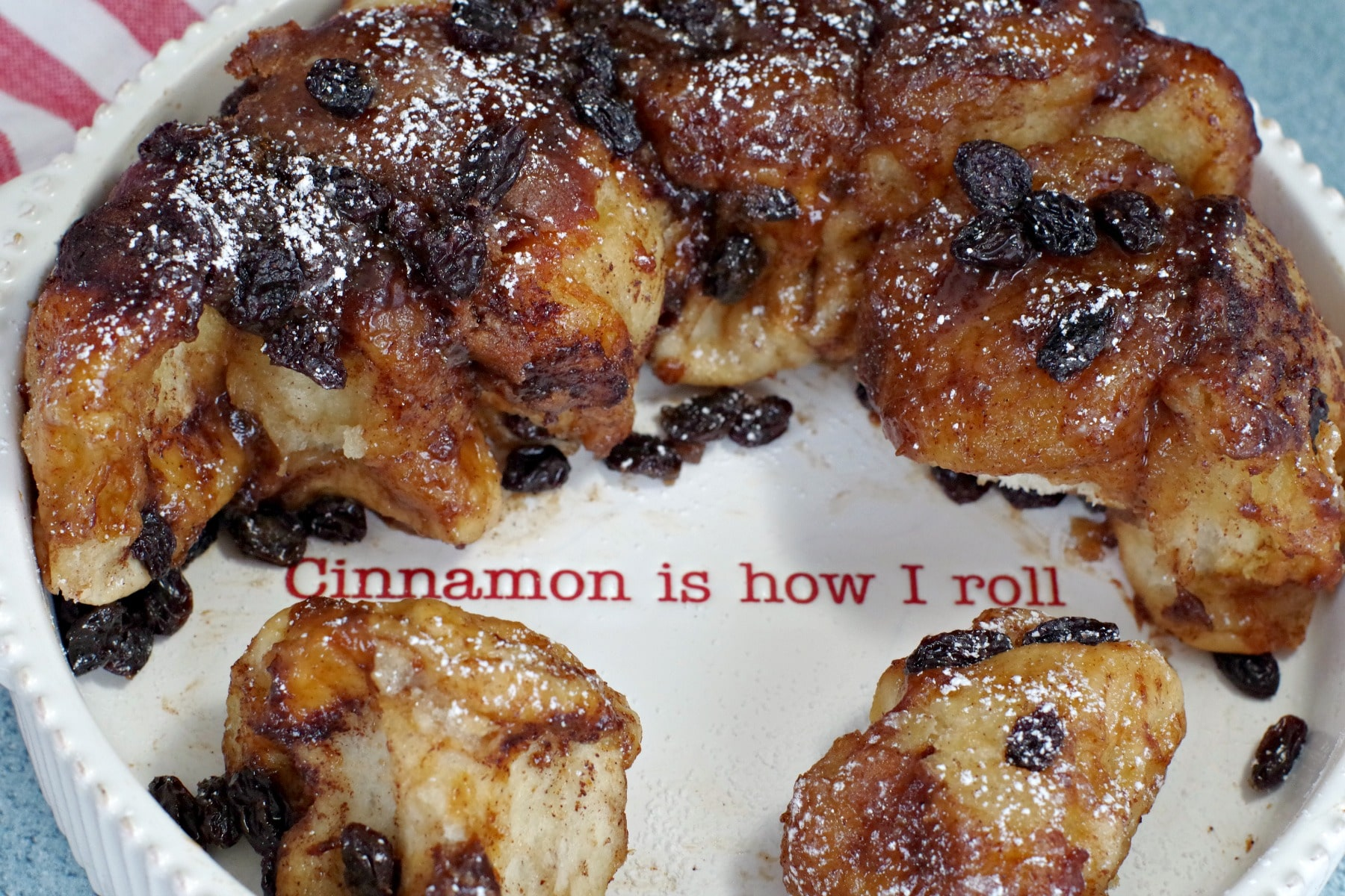 "Overnight Cinnamon Sticky Buns in white dish with writing ""cinnamon is how I roll)"