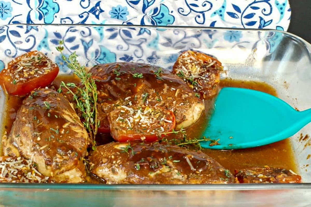 Balsamic chicken with tomatoes in a glass dish with an aqua blue spatula