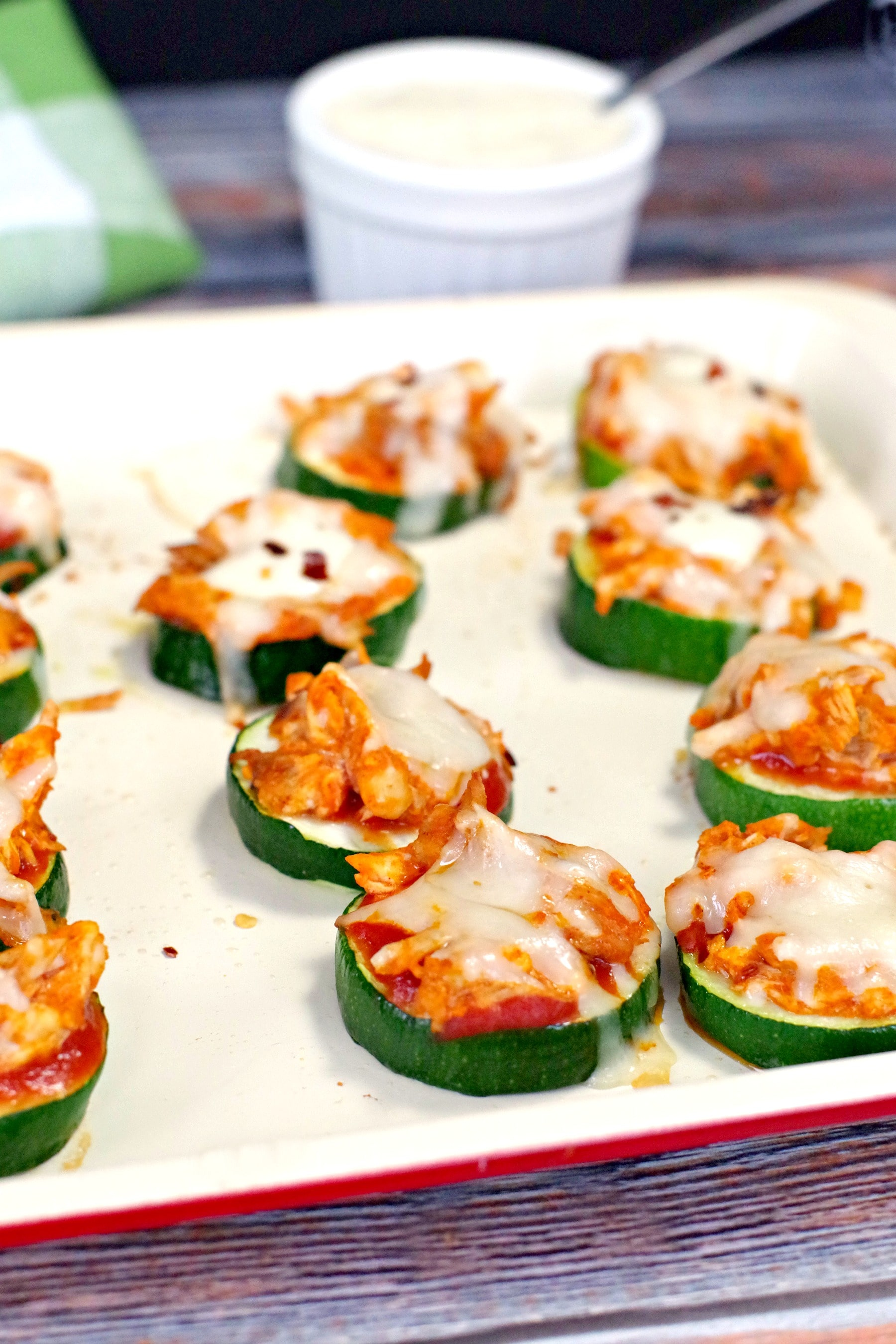 Buffalo Chicken Zucchini Pizza Bites on an off-white baking tray