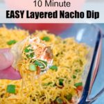 Pinterest pin with text at the top and photo of nacho chip being dipped into layered nacho/taco dip