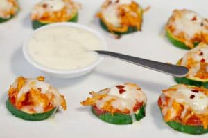 buffalo chicken zucchini pizza bites on white platter with ranch dip in bowl