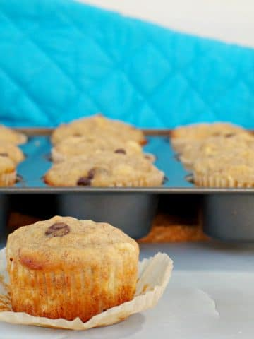 Healthy Banana Chocolate Chip muffins with pineapple in a muffin tin in background with muffin (with liner off) in front