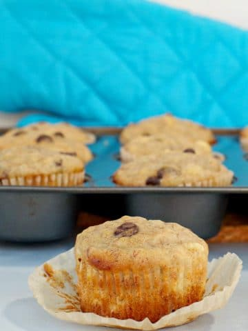 healthy chocolate chip banana muffins in muffin tin in background, with muffin on wrapper in front