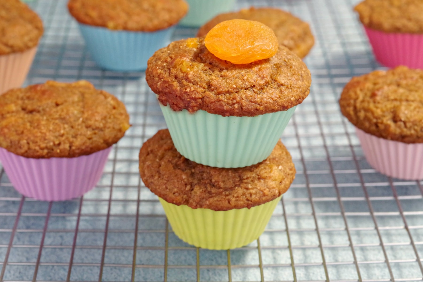 2 pumpkin bran muffins with an apricot on top and more muffins in background