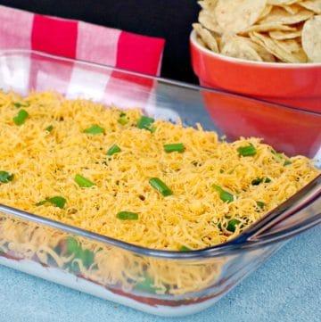 layered nacho dip in glass dish with nachos in orange bowl