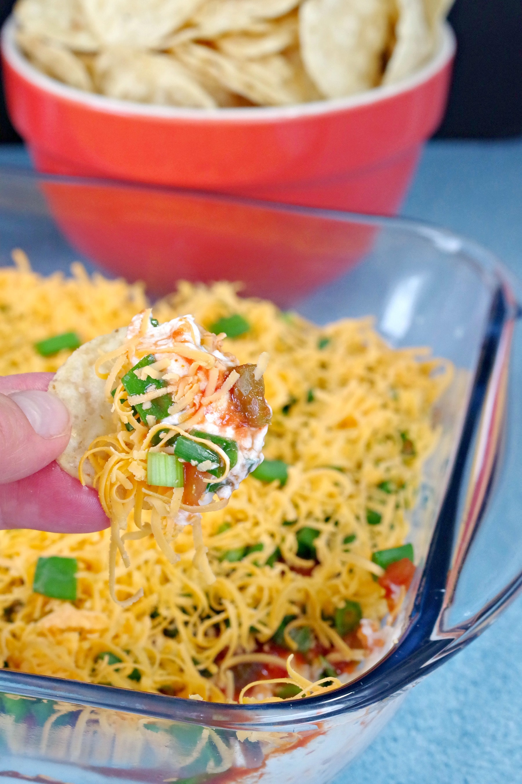 chip being dipped into layered nacho/taco dip