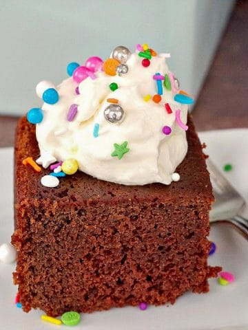 Old fashioned chocolate sour cream cake on a white plate with whipped cream and sprinkles on top and fork on the side