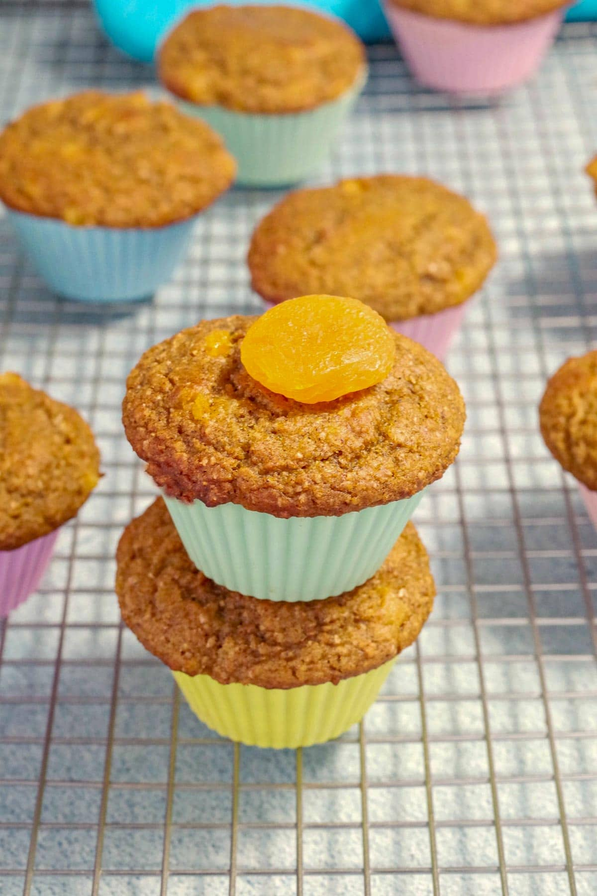 2 pumpkin bran muffins stacked on top of each other on a cooling rack