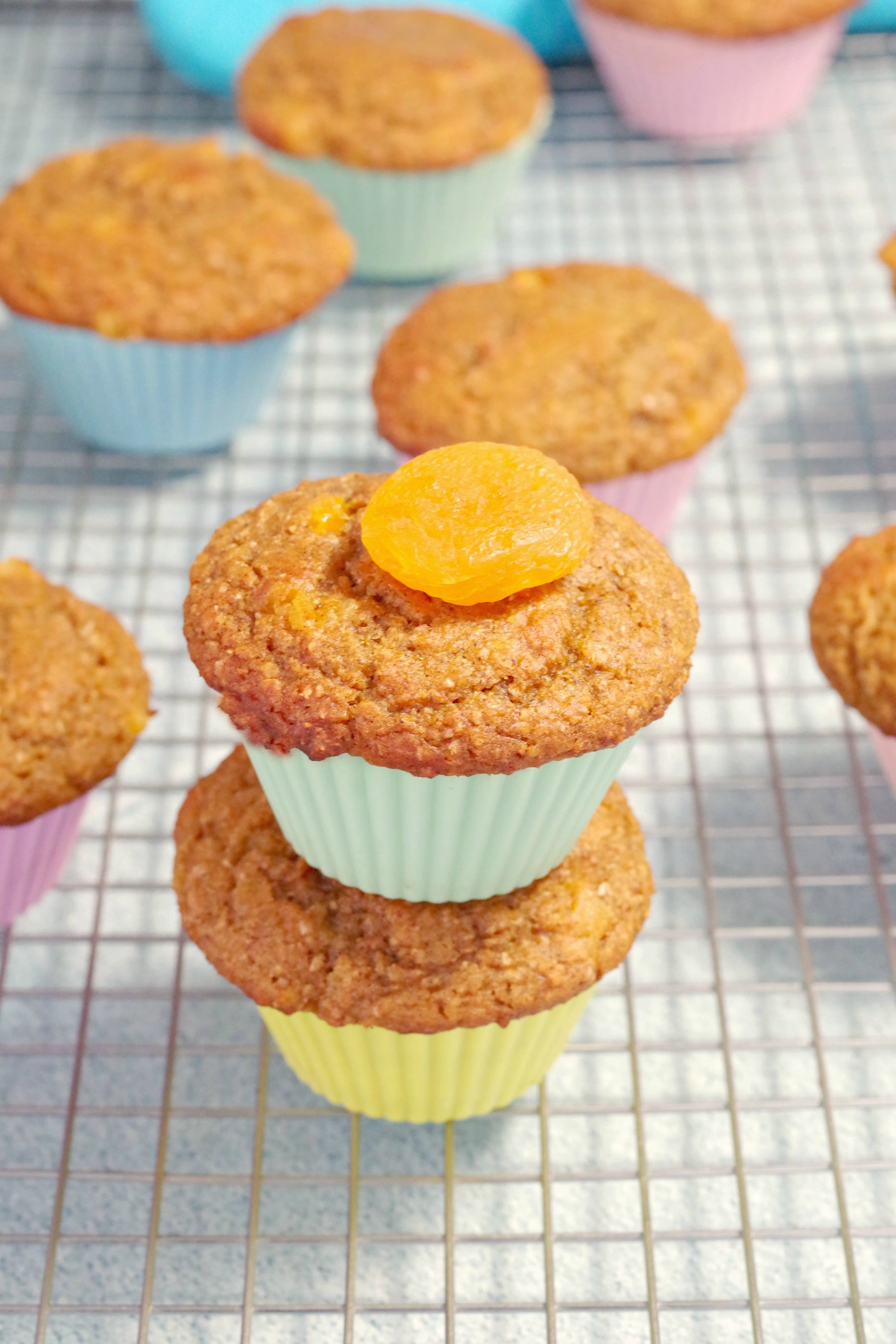 pumpkin bran muffins stacked on top of each other with dried apricot on top