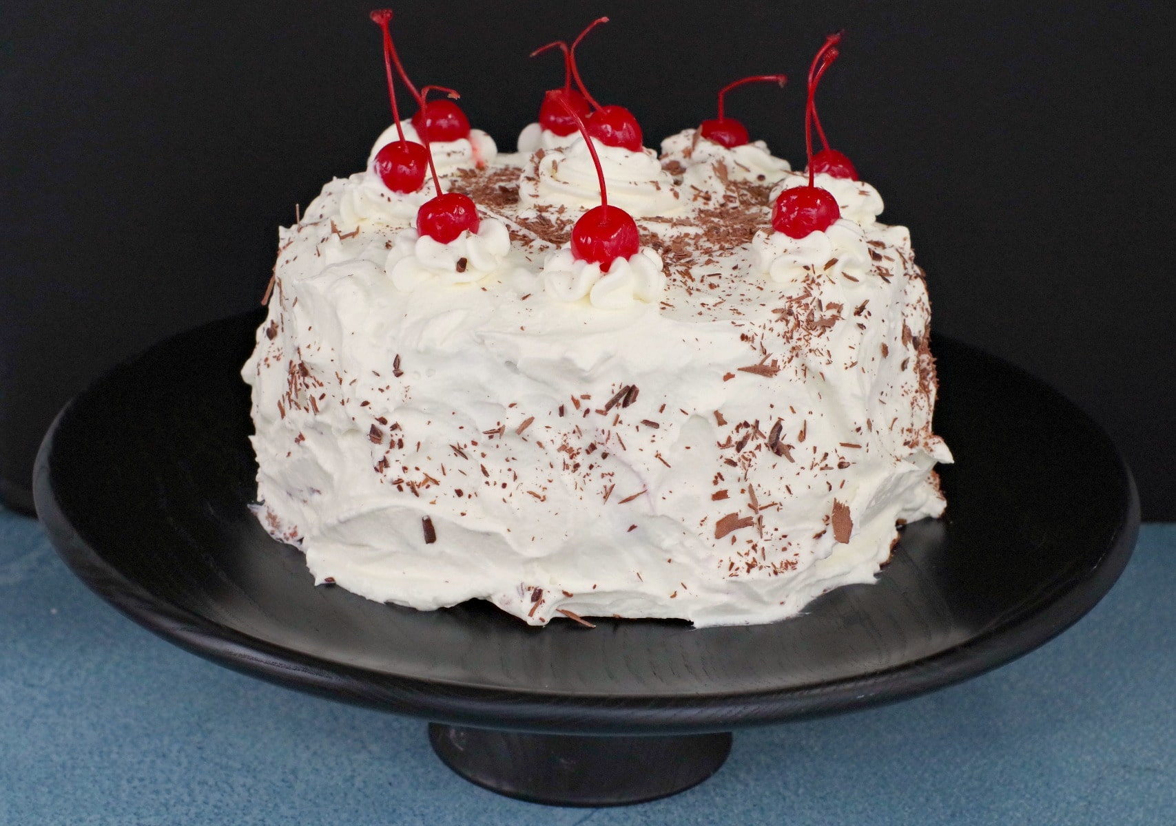 Whole black forest cake on black stand