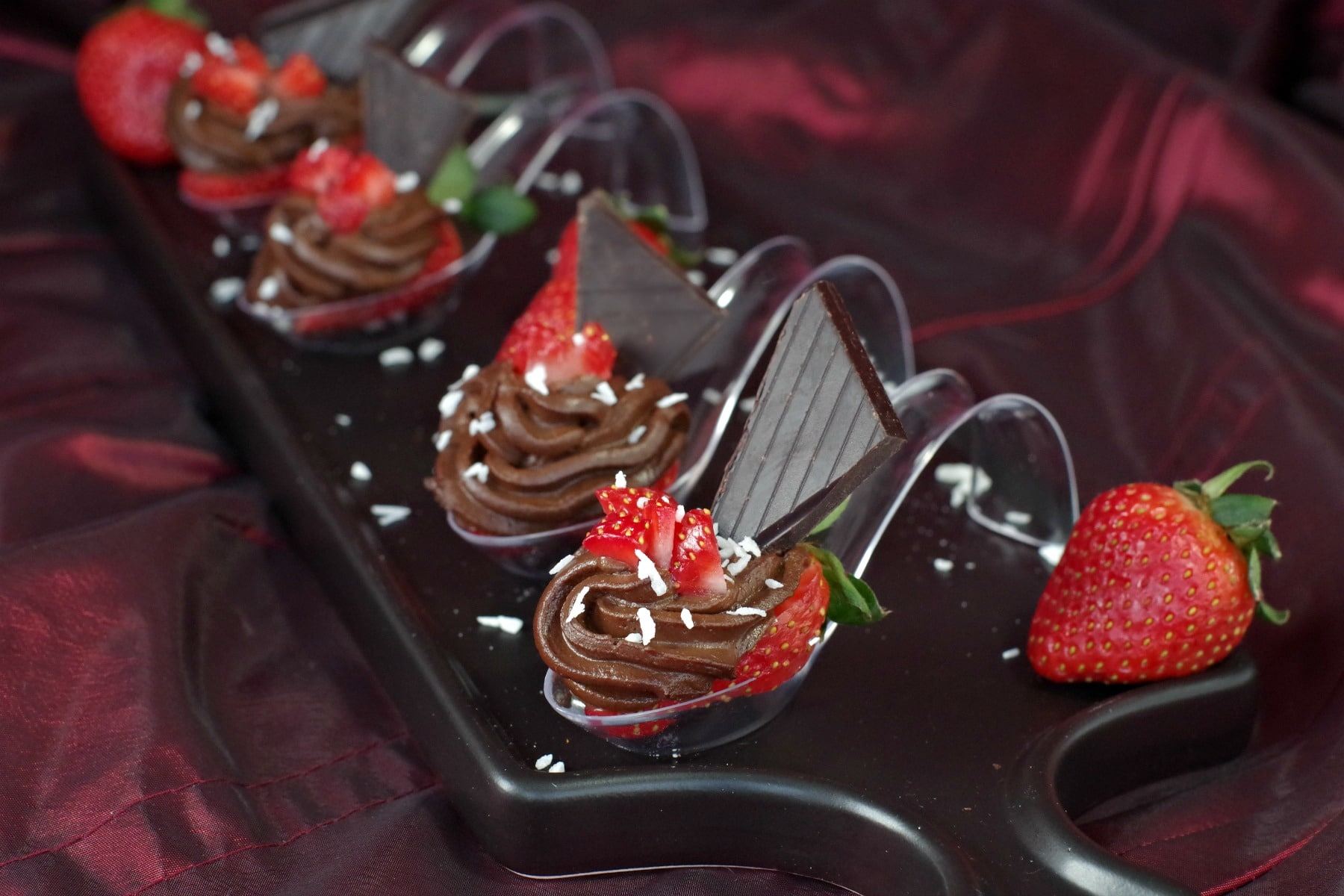 4 Chocolate Avocado strawberry desserts on spoons on a black appetizer tray
