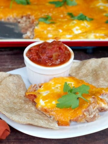 Huevos Rancheros on a white plate with tortillas and salsa and sheet pan (with more) in background