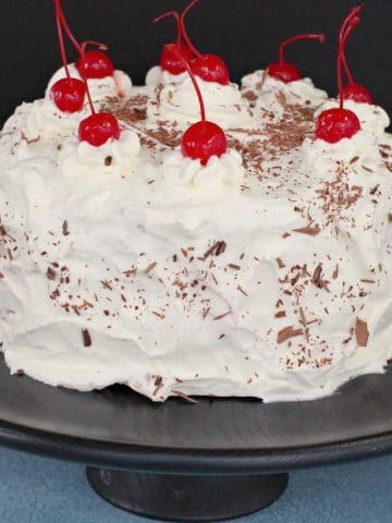 whole black forest cake on black cake stand
