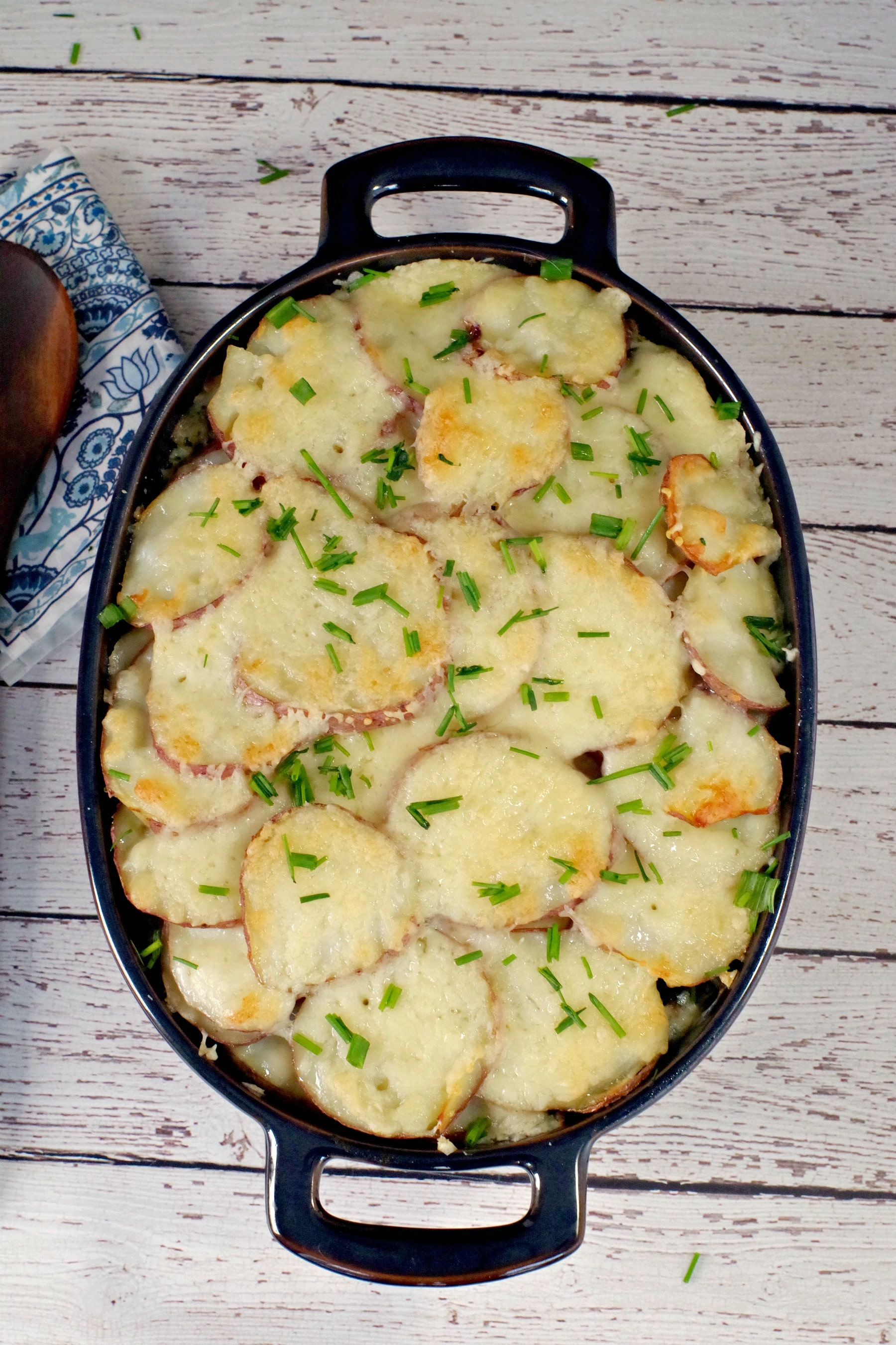 Potato casserole with spinach and beef in blue casserole dish