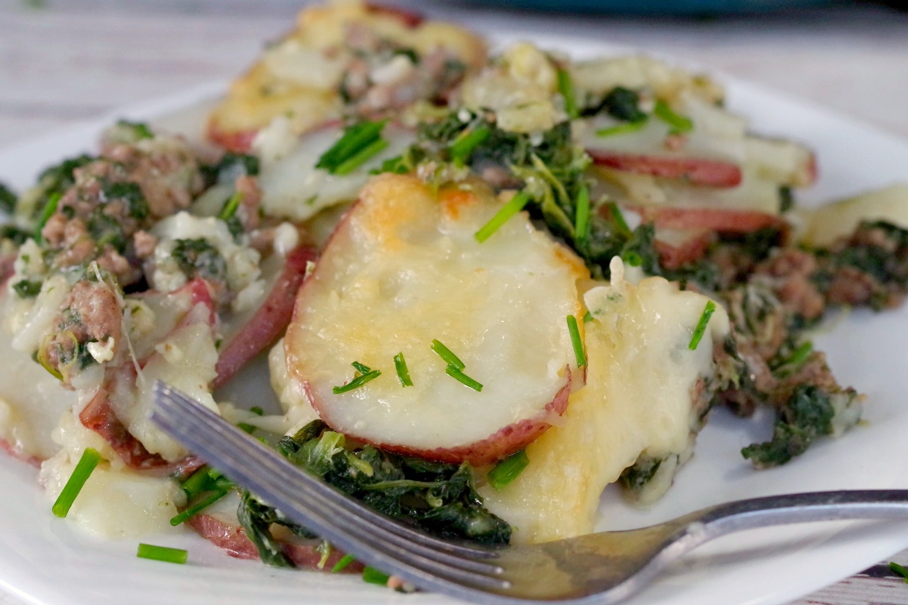 Close up of potato beef and spinach casserole on a white plate
