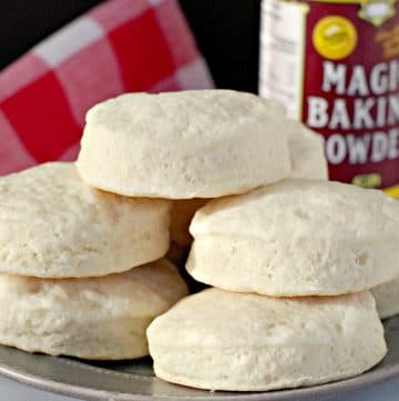 baking powder biscuits on a plate with baking powder in background