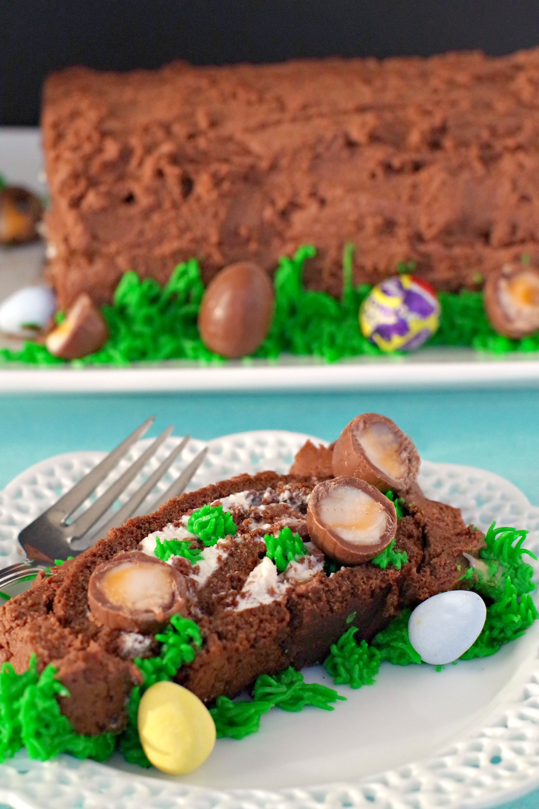 Easter Creme Egg Swiss Roll Cake on a white plate with cake in background